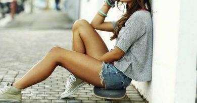 Femme skateuse assise sur son skateboard
